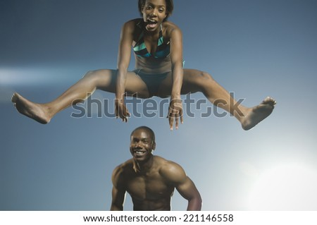 African American woman in bathing suit jumping over man