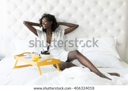 African american woman in white on the bed - stock photo