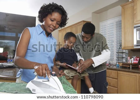 African American woman ironing clothes while man assisting son in homework - stock photo