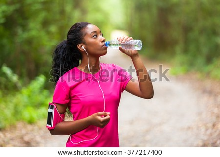 African american woman jogger drinking water  - Fitness, people and healthy lifestyle - stock photo