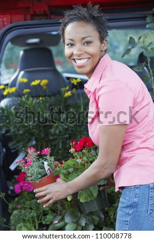 African American woman loading plants in car's boot - stock photo