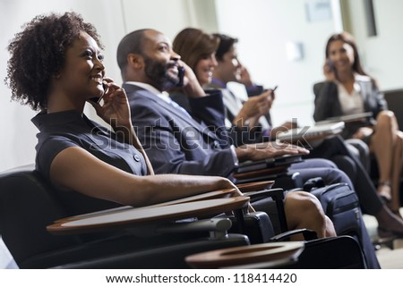 African American woman or businesswoman using cell phone in busy airport with other people in background - stock photo
