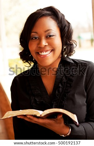 African American woman reading the Bible.