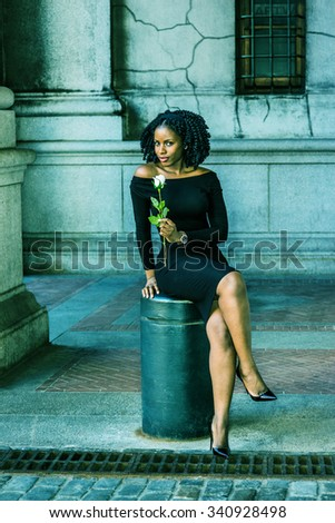 African American Woman seeking love in New York. Wearing long sleeve, off shoulder dress, holding white rose, a girl sitting on street, crossing legs, looking at you. Filtered look with green tint.