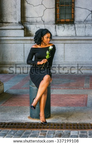 African American Woman seeking love in New York. Wearing long sleeve, slim, off shoulder dress, holding white rose, young black girl sitting on metal pillar on street, looking away, waiting for you.  - stock photo