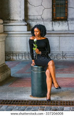 African American Woman seeking love in New York. Wearing long sleeve, slim, off shoulder dress, holding white rose, young black girl sitting on metal pillar on street, crossing legs, looking at you. - stock photo
