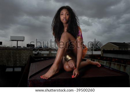 African American woman sitting on city rooftop, with buildings below.