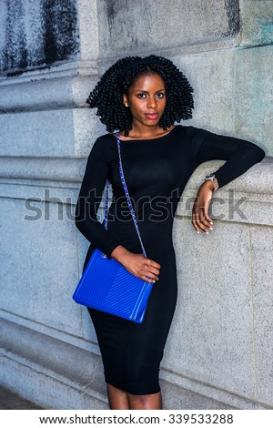 African American Woman street fashion in New York. Wearing long sleeve slim dress, wristwatch, carrying blue shoulder bag, a girl with braid hairstyle standing by wall. Filtered look with blue tint.  - stock photo