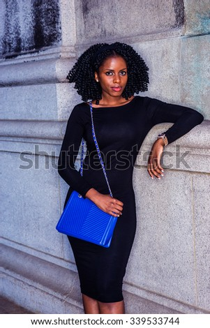 African American Woman street fashion in New York. Wearing long sleeve slim dress, wristwatch, carrying blue shoulder bag, a girl with braid hairstyle standing by wall. Filtered look with purple tint. - stock photo