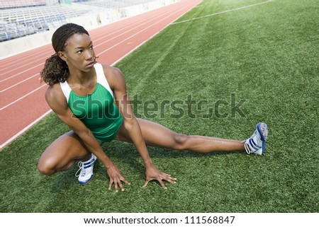 African American woman stretching before race on field
