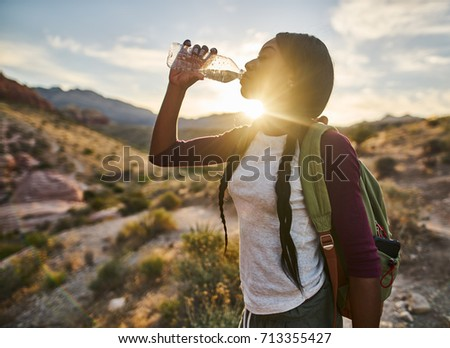 african american woman taking a break to drink from water bottle while hiking at red rock canyon nevada