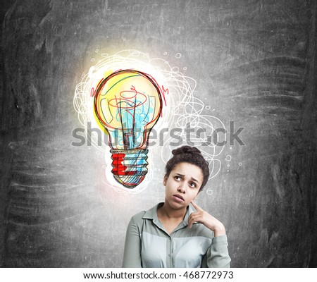 African American woman thinking about challenging idea near blackboard with colorful sketch of light bulb. Concept of new creative idea