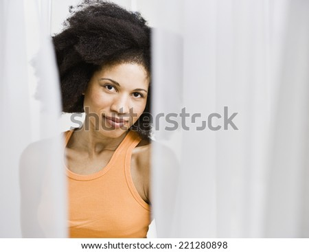 African American woman through parted curtains - stock photo