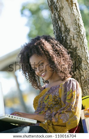 African American woman using laptop in college campus - stock photo