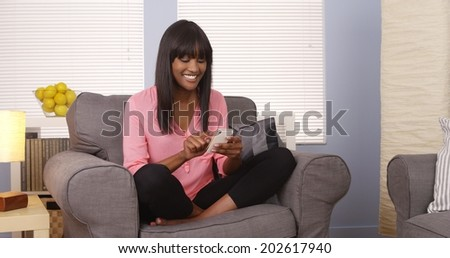 African American woman using smartphone at home - stock photo