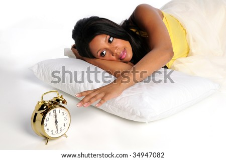 African American woman waking up extending hand to alarm clock - stock photo