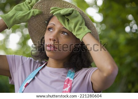 African American woman wearing gardening gloves - stock photo