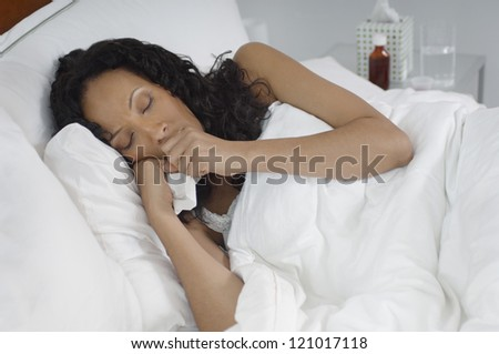 African American woman with flu lying in bed
