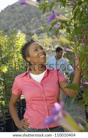 African American woman with man in background at botanical garden - stock photo