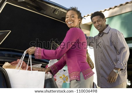 African American woman with man loading shopping bags in car - stock photo