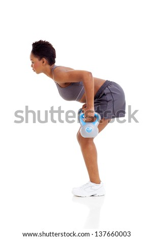 african american woman working out with kettle bell, isolated on white background