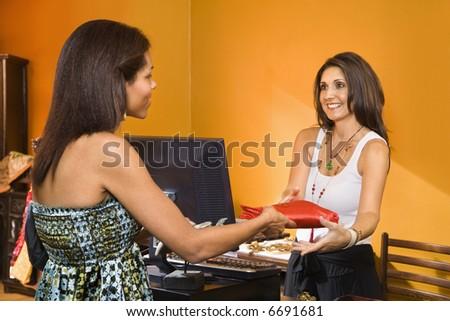 African American women handing item to sales clerk in boutique. - stock photo