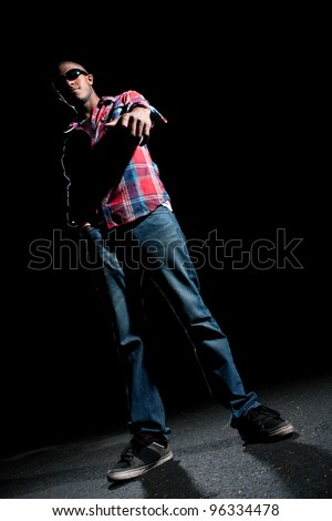 African American young man wearing sunglasses pointing at the viewer under dramatic lighting. - stock photo