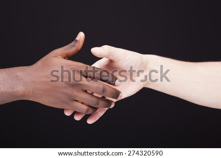 African and a caucasian man shaking hands over black background - stock photo