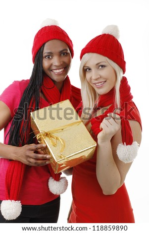 African and european woman with santa costume and christmas gift - stock photo
