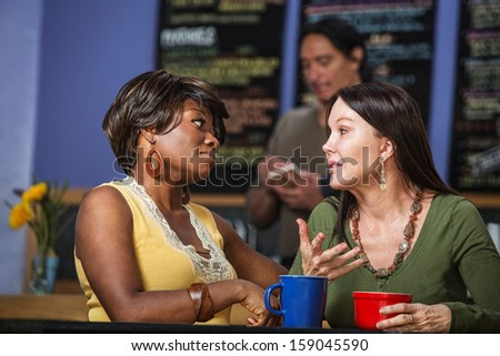 African and European women in a coffee house talking - stock photo
