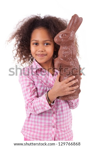 African Asian girl holding a giant chocolate rabbit, isolated on white background - stock photo