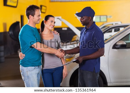african auto technician handshaking with young couple in garage - stock photo