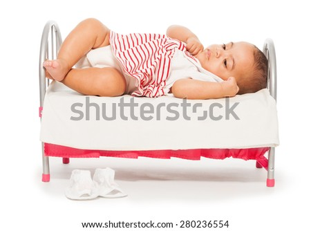 African baby in striped dress on the small bed - stock photo
