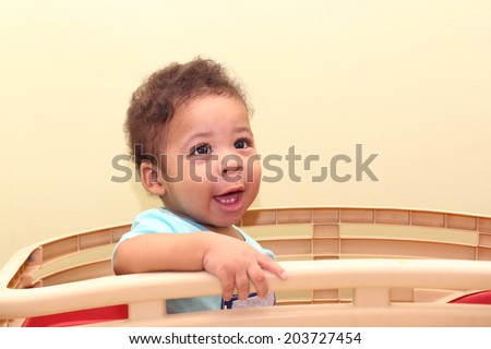 African baby sitting on his toy - stock photo
