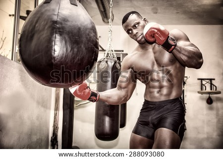 African black male boxer punching ball wearing boxing gloves in gym - stock photo