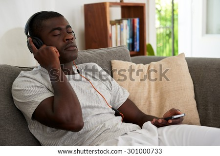african black man listening to music relaxing on sofa couch with mobile cell phone in home living room