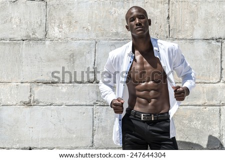 African black man model with six pack in unbuttoned white shirt, isolated against a concrete wall background on the beach - stock photo