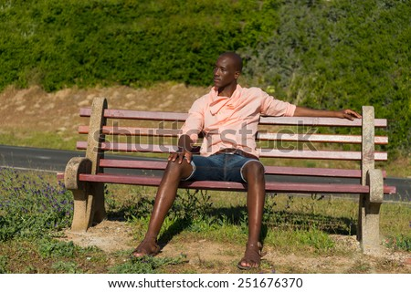 African black man sitting on wooden park bench, relaxing and stretching as he thinks