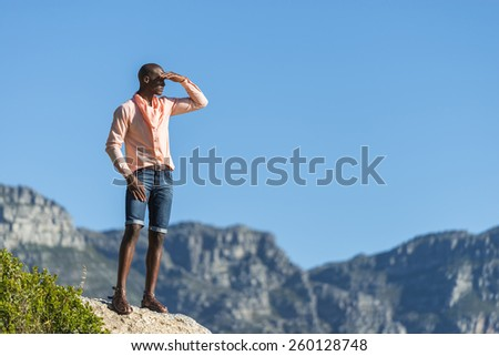African black man, standing on a high rock overlooking Cape Town as he points and scouts the blue sky, ocean and mountains on a sunny summers day - stock photo