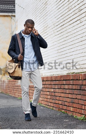 african black man walking and talking on cell phone in city on way to work - stock photo