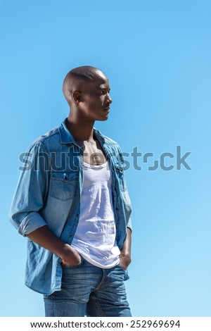 African black man wearing white vest and blue jean shirt with short jeans. Male model thinking while isolated alone by a blue ocean and sky background. Cape Town South Africa - stock photo