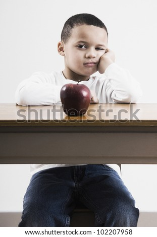African boy at desk with apple - stock photo