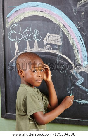 African boy drawing colorful picture on a blackboard in kindergarten - stock photo