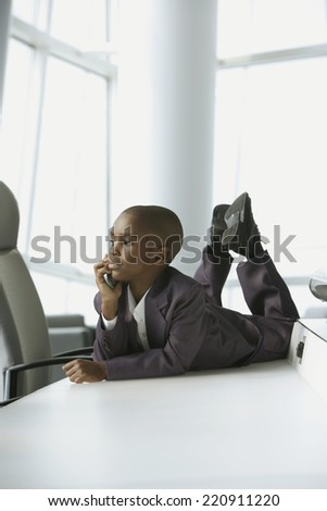 African boy in business suit laying on table in conference room - stock photo