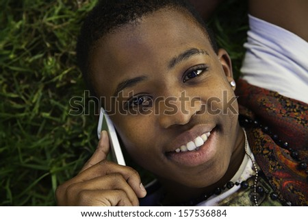 african boy on cell phone outside lying on grass