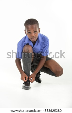 African boy wearing his school uniform ready to go back to school and tying his shoe.