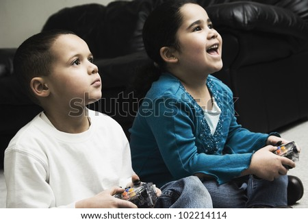African brother and sister playing video games - stock photo