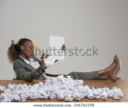 African business woman looking for workers . She is unhappy with cv of applicants and throwing crumpled papers with resume applications on table - stock photo