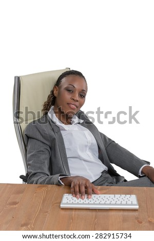 African business woman sitting at her desk and working isolated on white background - stock photo