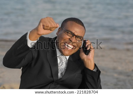 African businessman cheering on cell phone - stock photo